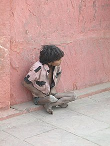 a poor boy sitting in the streets of Mumbai