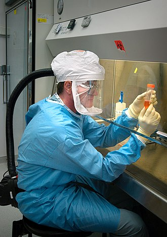 Biosafety level - Researcher at US Centers for Disease Control, Atlanta, Georgia, working with influenza virus under biosafety level 3 conditions, with respirator inside a biosafety cabinet (BSC).