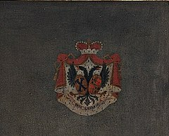 Red, white and blue coat of arms against a dark flat background