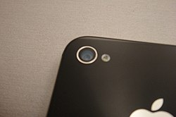 The camera on the back side of the iPhone 4S beside the iPhone 4 camera