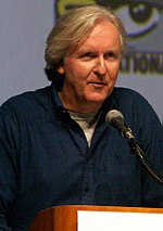 Photo of a grey-haired man wearing a black shirt speaking into a microphone.