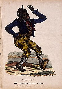 A man in blackface costumed in eccentric, formal clothes with patches, dances making exaggerated motions with one hand on hip.