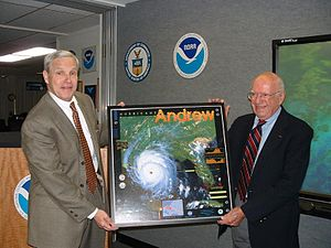 Herbert Saffir - NWS Director Jack Kelly presents Herbert Saffir (on right) with a framed poster of Hurricane Andrew depicting the Saffir–Simpson scale