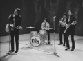 The rock band The Kinks in a TV show performance. From left to right are a singer/electric guitarist, a drummer behind a small drumkit, and two guitarists.
