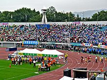 People cheering their teams with colorful flags for track and field games in a stadium