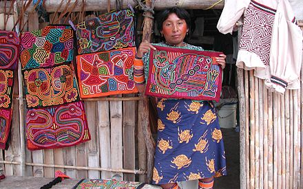 A Guma woman displays a selection of molas for sale at her home in the San Blas Islands. KunaWomanWithMolas.jpg