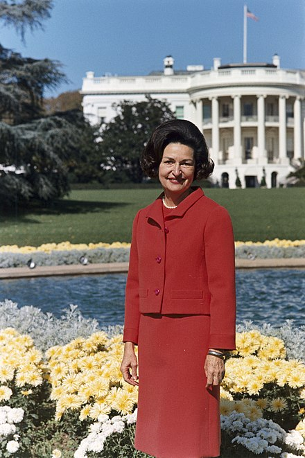 Lady Bird Johnson in front of the South Lawn of the White House Lady Bird Johnson, photo portrait, standing at rear of White House, color.jpg
