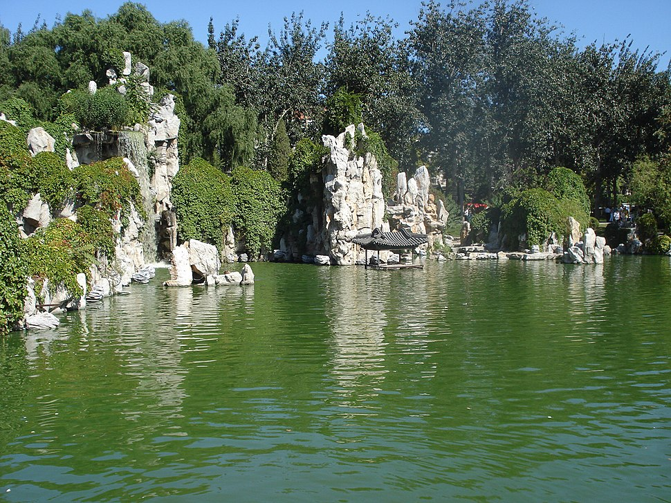 Rocky, bushy bluffs at the rear of some green water. There is a small structure with a Chinese roof at the base of one, in the center