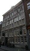 foto van Hoekhuis met lijstgevels, voorzien van horizontale profiellijsten, verticale reliefbanden en kruis- en twee- lichtkozijnen van Naamse steen.