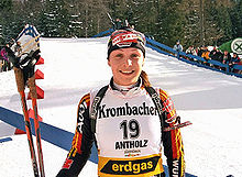 A young woman in multicoloured winter sportswear and with the number 19 on her jersey smiles into the camera, standing in a field covered with snow. A forest and many onlookers can be seen in the background. She holds ski poles in her right hand and has a rifle on her back.