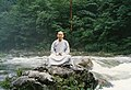 Man sitting on rock in a stream.jpg