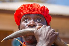 Man using horn of cow to make beautiful sound for his tribe mate to dance.jpg
