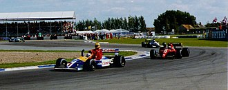 Williams Grand Prix Engineering - 1991 British Grand Prix winner Nigel Mansell giving Ayrton Senna a lift back to the Silverstone paddock after Senna had run out of fuel
