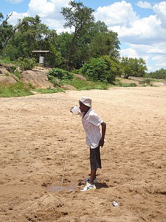Maranda, Zimbabwe - A young woman drinks water dug from the sand of the Mushawe alluvial aquifer. The pump for the Maranda water supply is in the background.