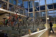 Side view of bikes parked in indoor bike racks, with tall windows beyond the racks