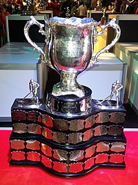 A silver cup attached to a large black base with several medallions each engraved with the name of the team and players for each successive champion.