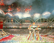 Crowds of people are gathered in a stadium with fireworks.