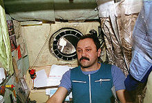 A man, dressed in blue work clothing, seen in a small cubicle. On the walls around him can be seen a sleeping bag, children's drawings, technical manuals and stained insulation. A small porthole in the centre of the wall behind him shows the nose of the Space Shuttle Atlantis and the blackness of space.