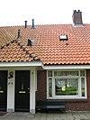 foto van Blok met 8 woningen, gecombineerde toegangen van twee woningen onder een ingestoken schilddak, zijkant met houten topgevel, aan zuidkant toegangspoort tot binnenterrein, onderdeel van complex bejaardenwoningen in Tuindorp Nieuwendam