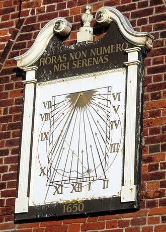"Sundial - SSW facing, vertical declining sundial on the Moot Hall in Aldeburgh, Suffolk, England. The gnomon is a rod that is very narrow, so it functions as the style. The Latin motto loosely translates as ""I only count the sunny hours."""