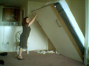 Murphy bed - A person operating a Murphy bed.