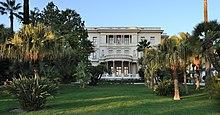 Vue d'un jardin avec palmiers au fond duquel une bâtisse blanche imposante à toit plat et entrée à colonnes se détache.
