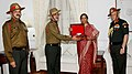 Nirmala Sitharaman receiving the urn containing the sacred soil of two soldiers of 39 Garhwal Rifles from their resting place at Laventie, France from Brigadier Inderjit Chatterjee.jpg