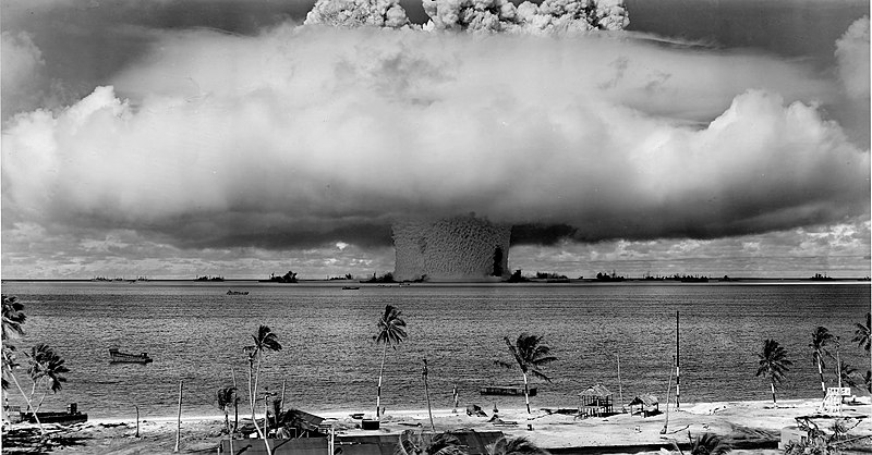 a spread out mushroom cloud in the ocean by a beach with some houses