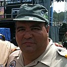 A Hispanic male wearing a beige colored button-up shirt and green cap posing for a picture outdoors.