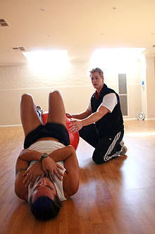 Personal trainer assisting and correcting a client during a fitball stretching exercise.jpg