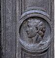 Piazza cattaneo, portale in pietra nera con medaglioni di imperatori e fregio con girali, delfini, e putti reggistemma, xvi secolo 09.jpg