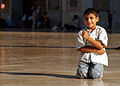 Playful boy in the expansive courtyard of the Great Umayyed Mosque of Damascus, Syria.jpg