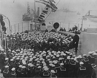 John S. McCain Sr. - McCain as a young ensign listens to President Theodore Roosevelt as he stands on a gun turret to address the officers and men of the USS Connecticut (BB-18), upon its return as a part of the Great White Fleet in February 1909 in Hampton Roads, Virginia