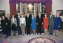 Husbands and wives alternate, as the subjects of the photo line up for the shoot, with the Presidential Seal in the foreground.
