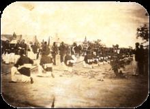 Uma fotografia velha que mostra uma procissão passando entre fileiras de soldados com tendas em segundo plano