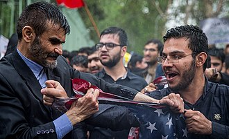 Anti-Americanism - Two protesters in Iran tearing a U.S. flag at an anti-American rally after the United States withdrawal from the Joint Comprehensive Plan of Action