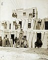 Pueblo Indians in front of a three storey Pueblo housing reproduction in the Department of Anthropology at the 1904 World's Fair.jpg