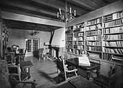 A black and white image of a room with a wood panelled ceiling, with a large fireplace and bookshelves on two sides of the room. At the far end of the room is a glass fronted double door leading away. There are a number of small chairs and tables around the room.