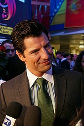 Smiling young man in brown suit, green striped shirt and green tie, being interviewed