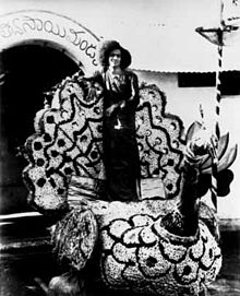 Sathya Sai Baba standing on a float in a parade.