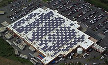 Aerial view of dozens of solar panels distributed around the roof of a Walmart store