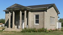 One-story concrete-block building, fairly small; pedimented porch with four columns
