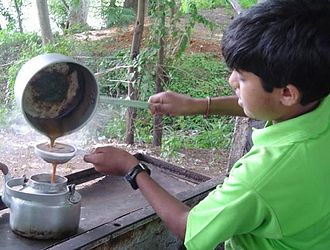 Masala chai - A boy in Mysore, India preparing masala chai: As it is prepared by decoction, preparation usually includes straining tea from the solids.