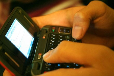 The popularity of mobile phones and text messaging surged in the 2000s in the Western world. Texting.jpg