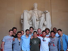 A thirteen-man group posing in front of the Lincoln Memorial.
