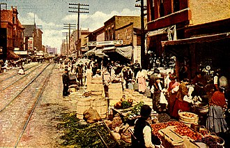 Maxwell Street - A scene of Maxwell Street circa 1908. The image has been colorized and is taken from a souvenir guide to Chicago printed in 1908. Note the signage in Yiddish that reads 'Fish Market'.