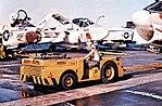 Tractor pulls an A-7E Corsair II aboard USS Coral Sea (CVA-43), in 1973.jpg