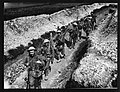 Troops in steel helmets moving along a communication trench fully equipped for their various duties (4688506660).jpg