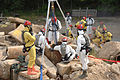 U.S. Airman and Soldiers work together to move large pieces of concrete during a joint combat training exercise June 26, 2008, at Fort Pickett, Va., involving chemical and biological warfare 080626-A-BB257-076.jpg