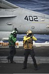 U.S. Navy Aviation Boatswain's Mate (Equipment) 3rd Class Meagan Rowland, left, guides an F-A-18C Hornet aircraft assigned to Marine Fighter Attack Squadron (VMFA) 323 onto a catapult as Aviation 131123-N-AZ866-009.jpg